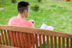 Asian man relaxing in a garden Royalty Free Stock Photo