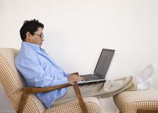 Asian man relaxing with laptop Stock Images