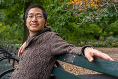 Asian man relaxing on a park bench Royalty Free Stock Photo