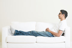 Asian man resting and daydream on couch Stock Photos