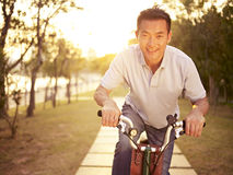 Asian man riding bike outdoors at sunset. Mid-adult asian man riding bicycle outdoors at sunset, smiling and happy, fitness, sport and exercise, healthy life and stock photo