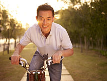 Asian man riding bike outdoors at sunset Royalty Free Stock Photo