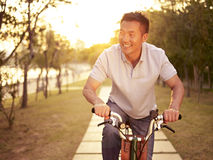 Asian man riding bike outdoors at sunset. Mid-adult asian man riding bicycle outdoors at sunset, smiling and happy, fitness, sport and exercise, healthy life and stock photography