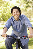 Asian man riding bike in park Royalty Free Stock Photo