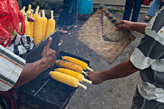 Asian man roasts and sells corn on street near Stock Images
