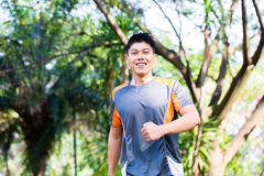Asian man running in city park Stock Image