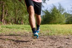 Asian man running on forest path during sunset, close up legs and feet.  royalty free stock photography