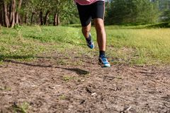 Asian Man running on forest path during sunset, close up legs and feet.  royalty free stock image