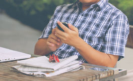 Asian Man& x27;s Hand Touching Smart Phone With White Laptop. Royalty Free Stock Photography
