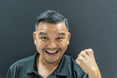Asian man success or great in dark style. Asian man 40s have a short hair with a beard in black polo shirt have a great and yes gesture with success and cheerful Royalty Free Stock Images
