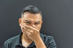 Asian man prevent stench on background dark style. Asian man 40s have a short hair in black polo shirt make gestures off their nose and mouth to prevent stock images