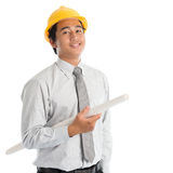 Asian man with safety hardhat. Portrait of attractive Southeast Asian engineer with yellow hard hat and blue prints smiling, standing isolated on white Royalty Free Stock Photography