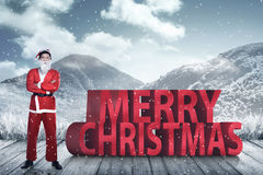 Asian man in santa claus costume standing with merry christmas text Stock Photo