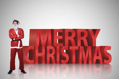 Asian man in santa claus costume standing with merry christmas text Stock Images