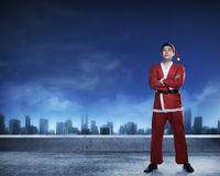 Asian man in santa claus costume standing on rooftop. Merry christmas concept Royalty Free Stock Image