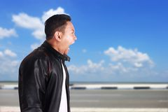 Asian Man Screaming Yelling Mad. Side view portrait of young Asian man wearing black leather jacket screaming mad yelling, over cloudy blue sky background Stock Photos