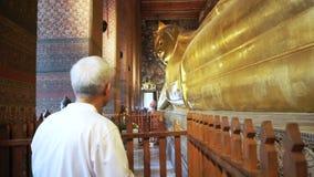 Asian man senior tourist visit Sleeping Buddha, Reclining Buddha statue in Wat Pho of Bangkok, Thailand stock video footage