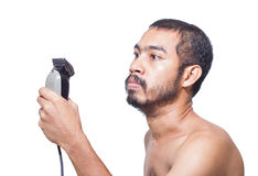 Asian man seriously hold hair clipper. Before cutting his hair by himself stock photo