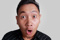 Asian Man Shocked with Mouth Open. Headshot portrait of young funny Asian man shocked surprised or terrified expression with mouth open, isolated on grey Royalty Free Stock Photos