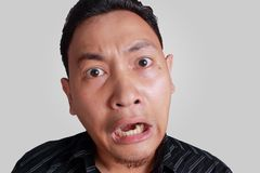 Asian Man Shocked with Mouth Open. Headshot portrait of young funny Asian man shocked surprised or terrified expression with mouth open, isolated on grey Royalty Free Stock Photo