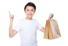 Asian man with shopping bag and finger point up Royalty Free Stock Images