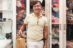 Asian man shopping bag in tailor fashion shop with. Clothes wardrobe Stock Photo