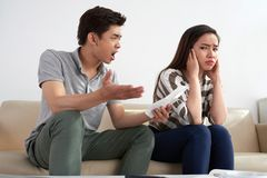 Asian Man Shouting at His Wife. Family quarrel: angry Asian men shouting at his young wife after received telephone bills, she closing her eyes with hands Stock Photo