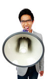 Asian man shouting with megaphone Royalty Free Stock Photography