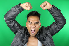 Asian man shouting. Young man shouting over a green background Stock Images