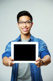 Asian man showing tablet computer screen Royalty Free Stock Images