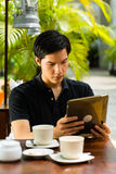 Asian man is sitting in a bar or cafe outdoor Royalty Free Stock Images