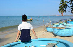 Asian man sitting on the beach. Asian man sitting on the basket boat and seeing the ocean in Vietnam Royalty Free Stock Photo