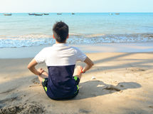 Asian man sitting on the beach Stock Images