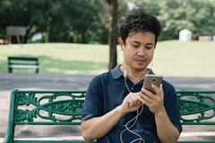 Asian man sitting on the bench with earphone in the garden.  Royalty Free Stock Image
