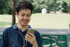 Asian man sitting on the bench with earphone in the garden.  Royalty Free Stock Photography