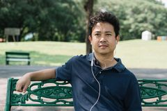 Asian man sitting on the bench with earphone in the garden.  Royalty Free Stock Images
