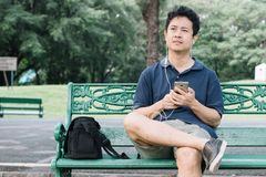 Asian man sitting on the bench with earphone in the garden.  Stock Images