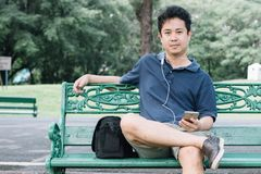 Asian man sitting on the bench with earphone in the garden.  Stock Photo