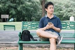 Asian man sitting on the bench with earphone in the garden.  Stock Image
