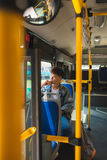 Asian man sitting in city bus, listening to music and looking th Stock Images