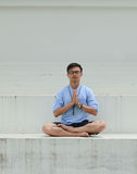 Asian man sitting on the floor and meditating Stock Photos