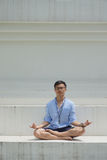 Asian man sitting on the floor and meditating Royalty Free Stock Image