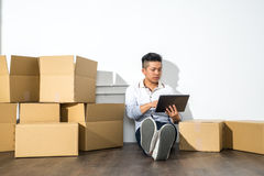 Asian man sitting on floor using his Tablet with boxes Royalty Free Stock Images