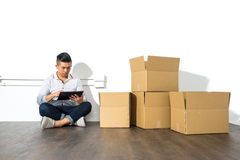 Asian man sitting on floor using his Tablet with boxes Stock Images