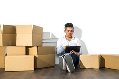 Asian man sitting on floor using his Tablet with boxes Royalty Free Stock Image