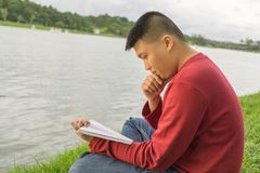 Asian man sitting on grass, reading book royalty free stock photo