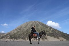 Asian man sitting on a horse with mountain background Stock Photos