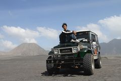 Asian man sitting on a jeep at desert Royalty Free Stock Images