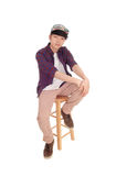 Asian man sitting and relaxing. A young Korean teenager sitting on a chair with a cap with his hands on his knee, isolated for white background Stock Images