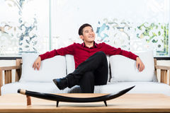 Asian man sitting on sofa in furniture store Stock Images